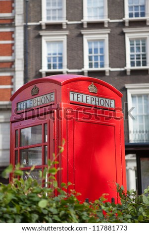 Traditional London symbol red public telephone box on residential district background, Great Britain - stock photo