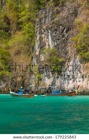 Traditional longtail boats in the famous Maya bay of Phi-phi Leh island, Thailand - stock photo