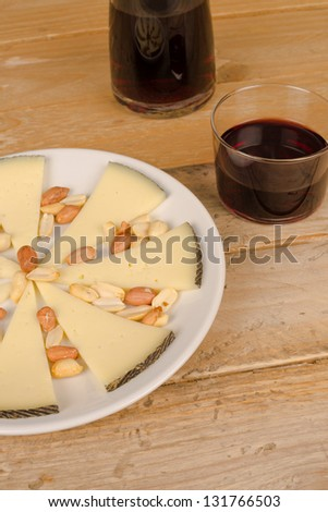 Traditional manchego cheese tapa served with red wine - stock photo
