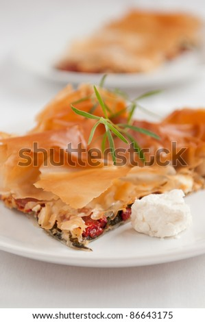 Traditional meal with filo dough, feta cheese, peppers, spinach - stock photo