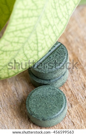 Traditional medicine: Green Eucalyptus leaves and pills on wooden background - stock photo