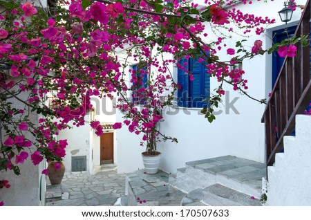 Traditional mediterranean house covered with pink flowers - Skiathos, Greece - stock photo