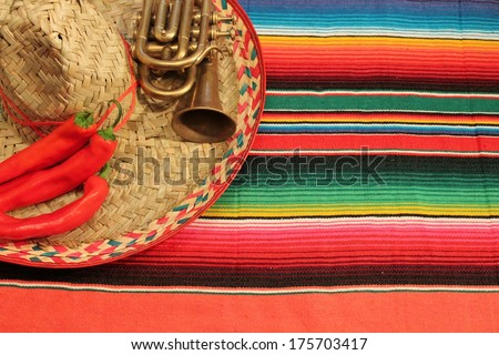 Traditional Mexican fiesta poncho rug  in bright colors with sombrero background with copy space - stock photo