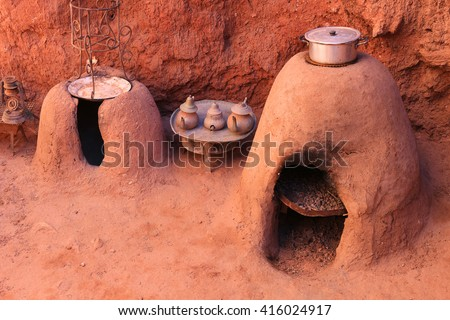 Traditional Moroccan earth ovens made out of sandstone with a pot cooking food  and tea kettles  - stock photo