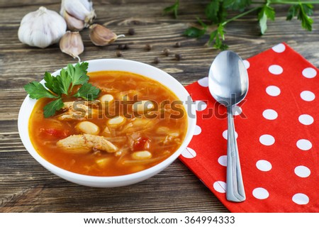 Traditional national Ukrainian beet soup borscht on the old wooden background. Soup with red beets, beans, cabbage, potatoes and meat. - stock photo