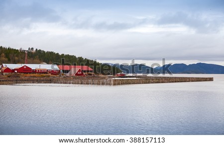 Traditional Norwegian fish farm with red wooden houses on the seacoast - stock photo