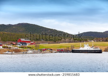 Traditional Norwegian small village with colorful wooden houses and ferry - stock photo