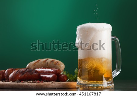 Traditional Oktoberfest menu. Beer in glass with foam, snacks, sausages grilled. On a green background with free space - stock photo