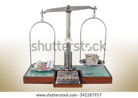 Traditional old style pharmacy scale with drugs heavier than money, small weights - stock photo