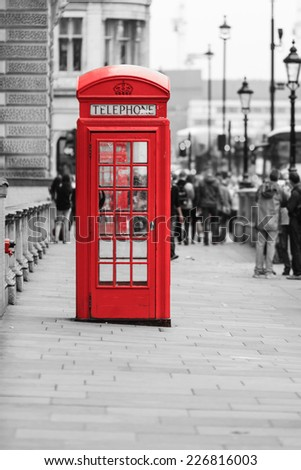Traditional old style red telephone box, british phone booth in London England UK. Black and white street. - stock photo