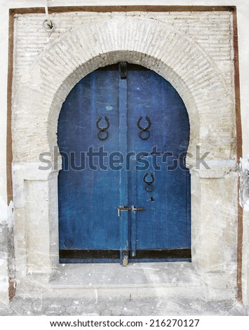 Traditional old Tunisian front door with a textured weathered look - stock photo