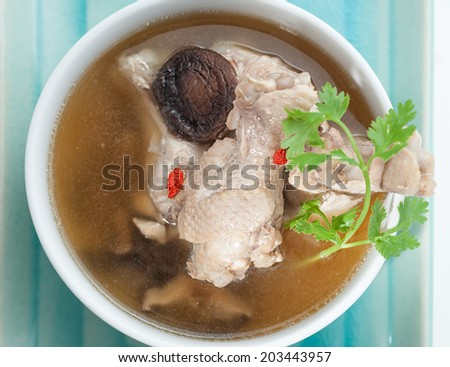 Traditional oriental chicken broth with mushrooms - stock photo