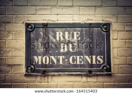 Traditional Paris plaque with street name on brick wall - vintage look - stock photo