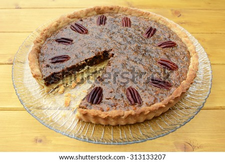 Traditional pecan pie on a glass plate with one slice taken - stock photo