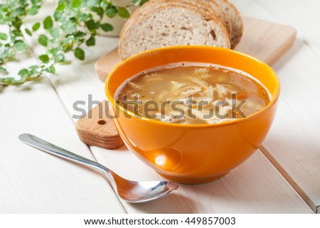 Traditional polish tripe soup with vegetables in orange bowl. - stock photo