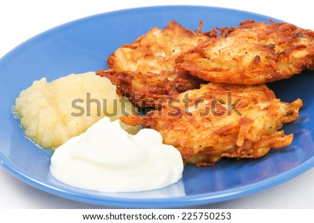 Traditional potato latkes or pancakes for Hanukkah with side of applesauce and sour cream - stock photo