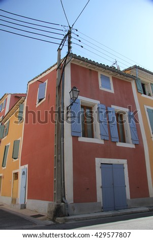 Traditional Provencal houses with plastered facades in bright colors in L'Isle sur la Sorgue - stock photo