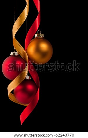 Traditional red and gold Christmas ball ornaments with ribbons on black - stock photo
