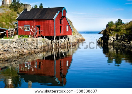 Traditional red house with reflection in Norway - stock photo