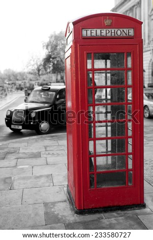 Traditional red phone booth in London with the Big Ben in the background at night - stock photo