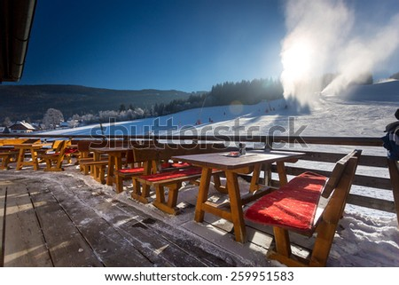 Traditional restaurant with open terrace on ski resort at sunny day - stock photo