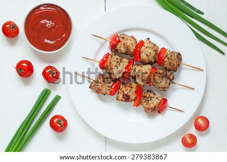 Traditional roasted turkey kebab skewer barbecue meat with vegetables and sauce on white dish. Served on kitchen table background. Rustic style, natural light. - stock photo