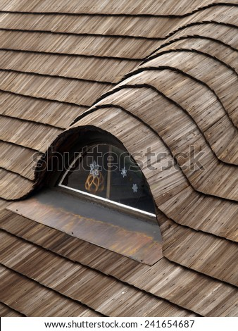 Traditional roof covered with shingles with window in an attic with Christmas decorations  - stock photo