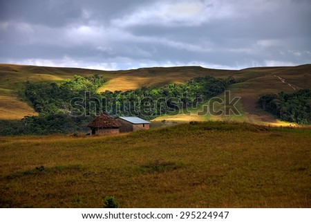 Traditional round hut with smoke from cooking fire in savanna with awesome patches of light on the grass - stock photo