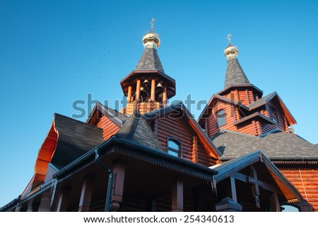 Traditional Russian and Ukrainian wooden orthodox church with lots of bells and gold crosses under the blue sky. The church is located in Kharkov in eastern Ukraine. - stock photo