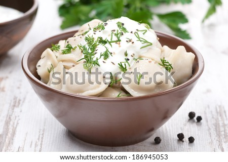 traditional Russian dumplings with sour cream and dill, close-up, horizontal - stock photo