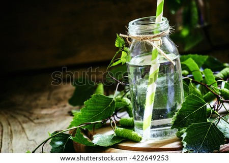 Traditional Russian refreshing drink birch juice in a small bottle, vintage dark wood background, selective focus - stock photo