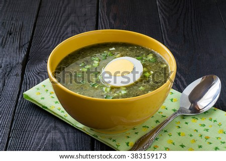 Traditional russian spring sorrel soup with egg in a yellow bowl on wooden table - stock photo