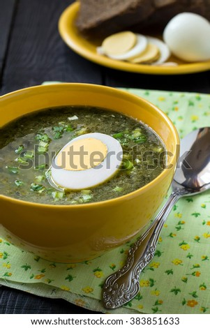 Traditional russian spring sorrel soup with egg in a yellow bowl, plate with rye bread and eggs, spices on a wooden table on wooden table. Selective focus - stock photo