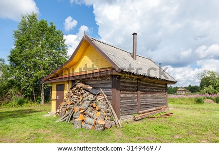 Traditional russian wooden bath at the bank of lake in summer sunny day - stock photo