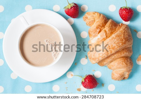 Traditional rustic croissant sweet French pastry and a cup of coffee latte with fresh strawberries on provence style background. Perfect breakfast or lunch. Natural light and rustic style. - stock photo