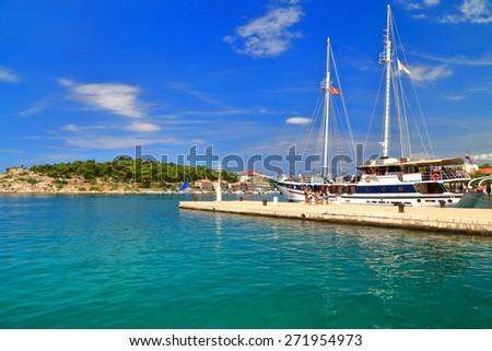 Traditional sail boat embarking tourists on sunny pier near the Adriatic sea, Makarska, Croatia - stock photo