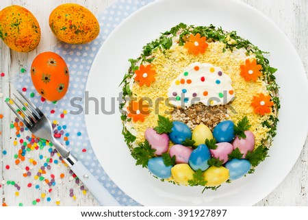 Traditional salad on Easter dinner table, creative idea for holiday snack food, edible decoration of colorful eggs top view - stock photo