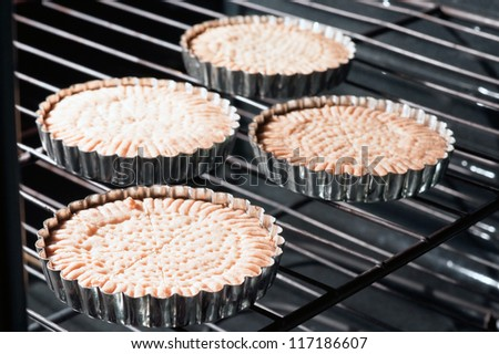 Traditional Scottish shortbread. Four freshly baked biscuit circles in baking tins in oven. Cut into petticoat tails (triangular shapes). Sweet treats for holidays such as Christmas and Easter. - stock photo