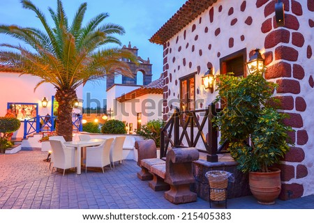 Traditional shops on street of Canarian village of Adeje at night, Tenerife, Spain - stock photo