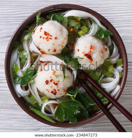 Traditional soup with fish balls and rice noodles close up. horizontal view from above  - stock photo