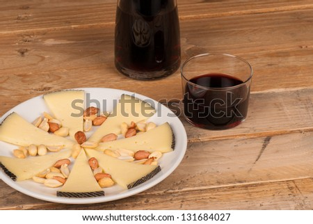 Traditional Spanish cheese tapa served with red wine - stock photo