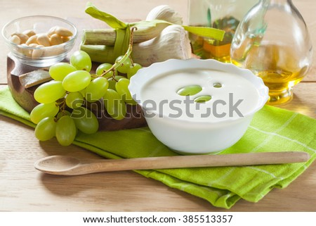 Traditional Spanish dish, cold soup ajoblanco (garlic with almonds, white wine vinegar and olive oil and grapes) in a white bowl with a spoon on a green napkin on a wooden table, horizontal - stock photo