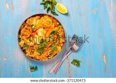 Traditional spanish paella dish with seafood, peas, rice and chicken over grunge blue background. Top view. Selective focus - stock photo