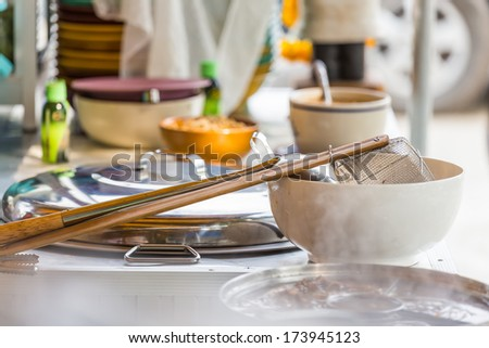 Traditional steel wire mesh noodle strainer and a hot noodle pot.Thailand. - stock photo