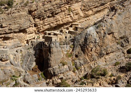 Traditional stone houses in a small cliff hamlet near Sroot in the Jebel Akhdar mountains of the Sultanate of Oman. - stock photo