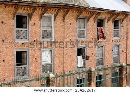 Traditional style carpets hanging on red brick walls of traditional newar style buildings-paint faded windows and roof struts. Dhulikhel-Kavrepalanchok distr.-Bagmati zone-Nepal. - stock photo
