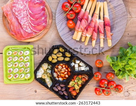 Traditional tapas, fast food with prosciutto, cheese, olive and sausage, top view - stock photo