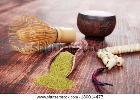 Traditional tea ceremony. Powdered green tea matcha, hot tea in ceramic cup, bamboo chasen and buddhist necklace on brown wooden background. - stock photo