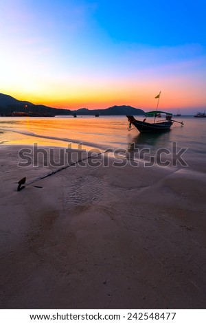 Traditional Thai boat at sunset in the sea near the shore of the beach. - stock photo