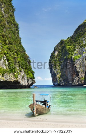 traditional Thai boats in the Maya Bay of Phi Phi island - stock photo